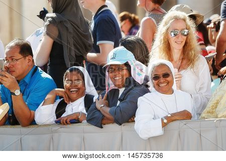 Rome, Italy - September 3, 2016: We are in Piazza San Pietro, during the celebrations of the holiness of Mother Teresa of Calcutta. Among the faithful who assist behind the barriers, even some nun, shooting this scene, happy to be present at the big event
