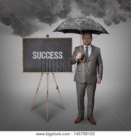 success text on blackboard with businessman holding umbrella