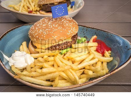 Plate with hamburger and fries - Food photography with a delicious big hamburger french fries mayonnaise ketchup and a little European Union flag on top.