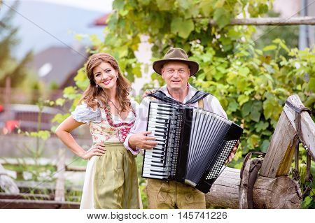 Couple in traditional bavarian clothes standing in green garden, man playing accordion. Oktoberfest.