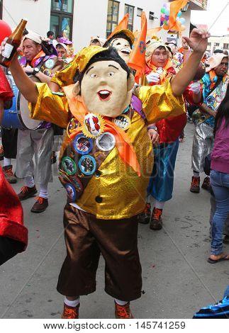 Cajamarca Peru - February 7 2016: Man in oversized mask and boy scout costume in Carnival parade in Cajamarca Peru on February 7 2016