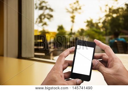 Hand of young man holding smart phone white screen on blurred livingroom decoration interior with copy space in morning light over the sun