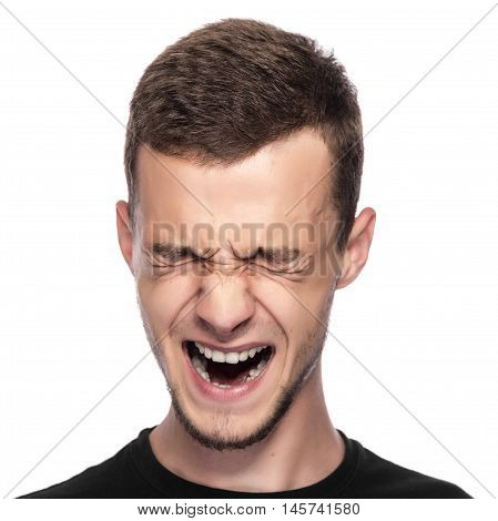 Young man screaming on a white background.