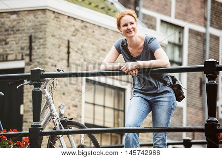 Smiling young woman resting on a bridge next to a parked bicycle in an old European town.