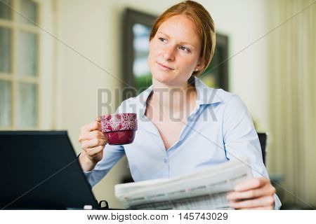 A young business woman reading the morning news at home over coffee.