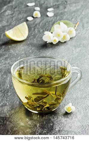 Cup of flavored japanese green tea with jasmine flowers and lemon on a black stone background. Focus is on the front of the cup.