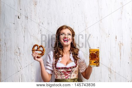 Beautiful young woman in traditional bavarian dress holding a mug of beer and pretzel, looking up. Oktoberfest. Studio shot on white wooden background.
