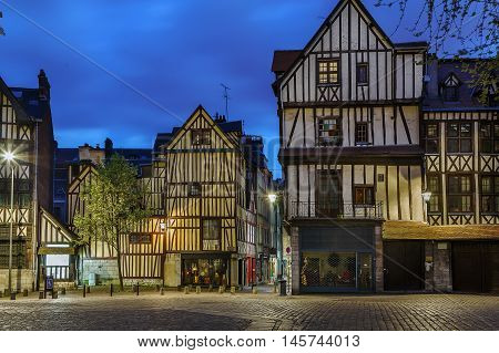 Street in historical center of Rouen with half-timbered houses France. Evening