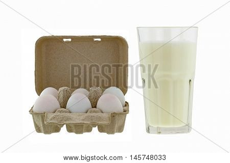 Paper pulp egg tray packages of fresh eggs next to glass of fresh pasteurized milk isolated on white background