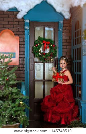 Little winter Princess in red dress with box-gift in hands welcomes New year and Christmas in enchanting holiday interior with decorated pine and Christmas wreath on door