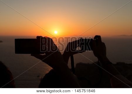 Silhouettes of people taking sunsets pictures with their smartphones