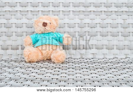 Closeup a fabric bear doll sit on wood weave chair texture background with copy space