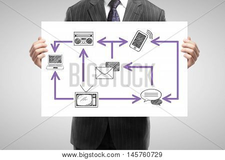 Closeup of businessperson in suit holding whiteboard with abstract technology network on light background. Communication concept