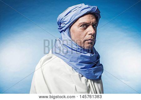 Profile View Of Berber Man Wearing Blue Turban With White Robe. Studio Shot.