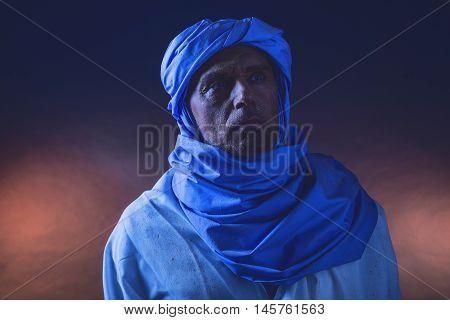 Berber Man In Night Light Wearing Blue Turban With White Robe. Studio Shot.
