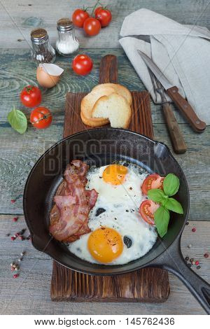 Fried eggs strips of bacon halved tomato and basil in a cast iron skillet on an old wooden table in rustic style