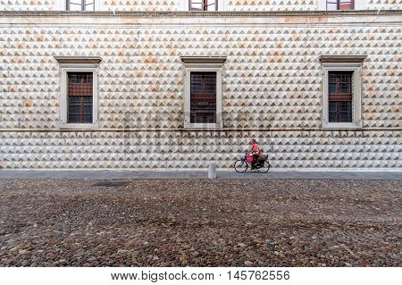 Ferrara Italy - August 21 2016. Woman on bicycle in front of the famous Palazzo dei Diamanti.