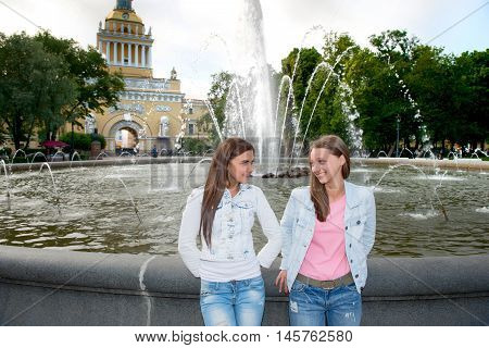 Two beautiful girls walking in the summer park end talking. Friends wearing stylish shirt and jeans enjoying day off and have fun.