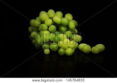 Fresh green grapes on a black background