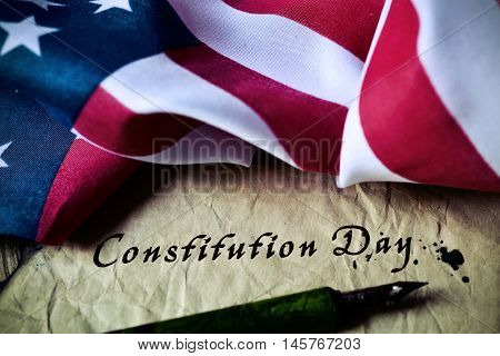 the text constitution day written with a dip pen in a yellowish piece of paper and the flag of the United States