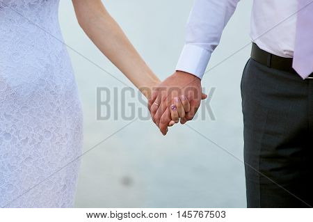 Wedding photo of bride and groom holding hands closeup