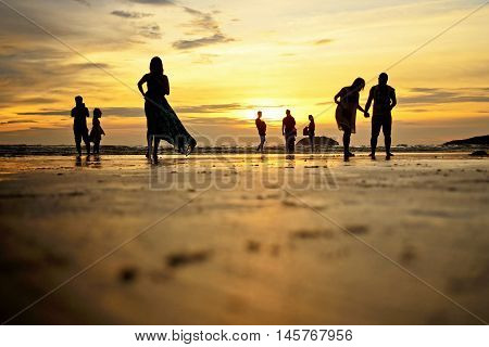 Low Angle And Selective Focus Shot Of Silhouettes Of Beach Goers Enjoying The Sunset At Tanjung Aru