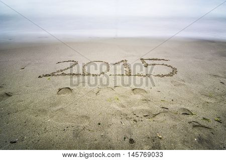 2015 written on the sand of a beach to the sea