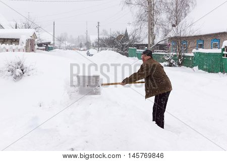 elderly man clears snow near the house