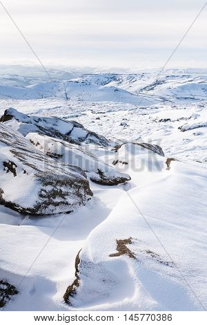 Snow covered tor landscape in winter Kinder Scout Derbyshire England UK