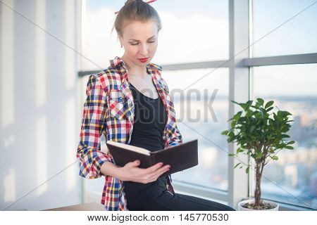 Side view portrait of young woman sitting, looking down, reading the book, learning at light room in morning with her torso turned