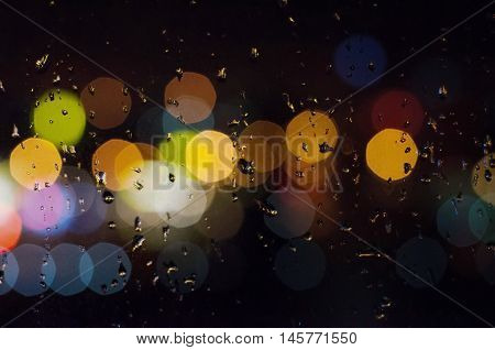 Raindrops on a window glass and bokeh from night city lights