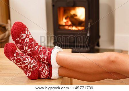 Womans feet in red Christmas socks by cozy wood burner