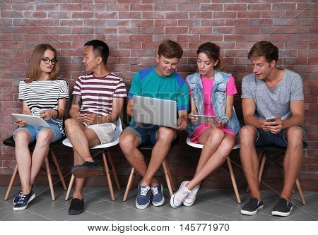 Young people with gadgets hanging out together