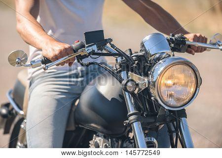 My bike is the best. Close up photo of guy sitting on motorcycle and holding handlebar, turning headlight