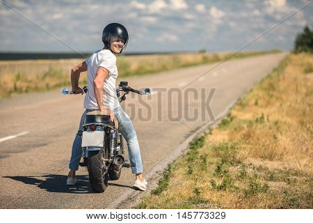 Ready for road trip. Young guy in helmet sitting by motorcycle, parking in side of road and looking at camera, smiling