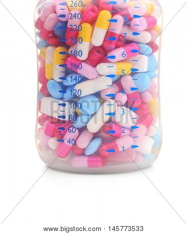 Baby bottle full of colourful pills isolated on white