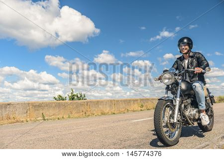 Ready for any challenge. Young man riding motorcycle on open road and smiling on background of sky and clouds