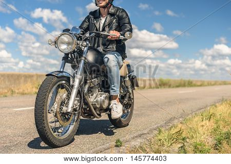 Nothing beats this feeling. Close up of young man wearing leather jacket and riding his bike on road and smiling