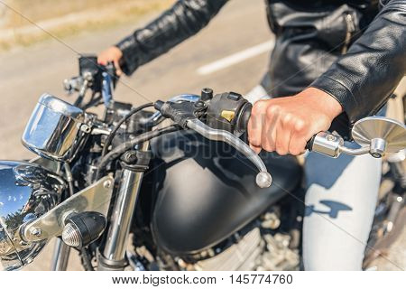 My bike is my life. Top view of motorcycle handlebar, which keeping by man in black leather jacket
