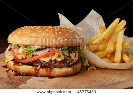 Cheeseburger (burger) with french fries and sauce. Hamburger on a brown wooden background