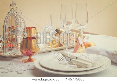 Tableware for christmas - plates, cups and utencils with white table cloth and christmas golden decorations, retro toned
