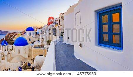 Oia town on Santorini island in Greece. Panoramic view of traditional and famous white houses and churches with blue domes over the Caldera, Aegean sea
