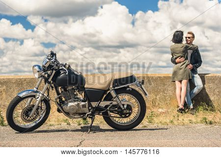 Just us and road. Shot of vintage motorcycle with young couple having intimate moment while out on road in background