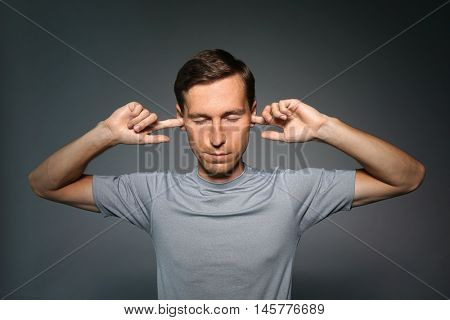Young man stopped his ears with fingers.