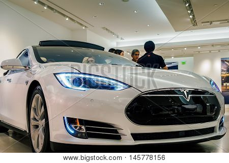 Honolulu, Hawaii, USA - Dec 21, 2015: White Tesla Model S70 electric vehicle on display in a showroom at Ala Moana Center. A sales consultant (back to camera) was talking to potential clients.