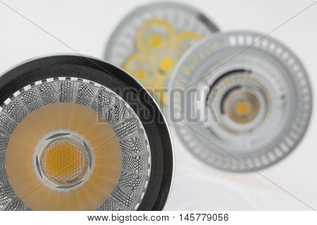 three LED GU10 bulbs with various plastic scattered light focusing on reflecting surface in the foreground