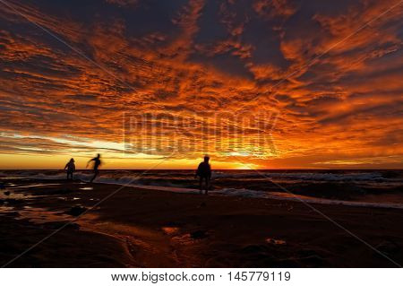 Sunset and dramatic clouds over the sea casts a glow on some indistinct human figures.