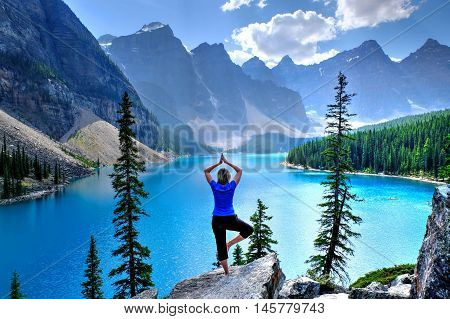 Woman relaxing on cliff at Moraine lake in Rocky Mountains. Banff National Park. Alberta. Canada.