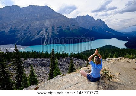 Woman meditating on cliff above Peyto lake in Rocky Mountains. Banff National Park. Alberta. Canada.
