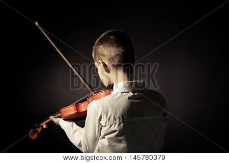 Rear View Of Child Playing Violin In Darkened Room